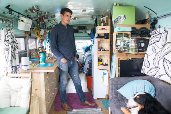 Justin Florian inside a converted bus named Biggie Bus that cost under $10,000 to purchase and renovate.