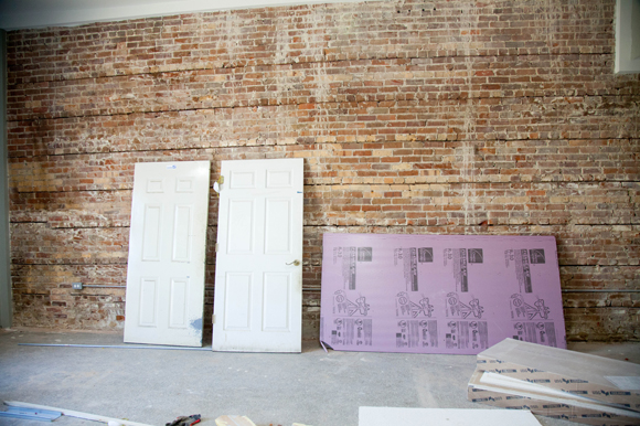 Exposed brick at a building being renovated for marketing, design, and a brew pub retail space.