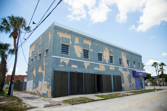 Exposed brick peers through blue painted exterior at the future home to retail and office sites in up-and-coming West Tampa.