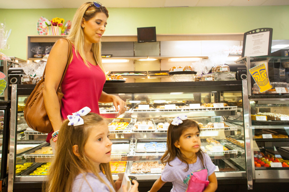 Maria Castillo and her girls Mia, and Maite, third and fourth generation West Tampa residents, pick out fresh-made cookies at the iconic Alessi Bakery.
