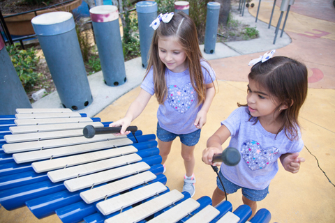 Mia and Maite experiment with sounds in the children's playground at Macfarlane Park.