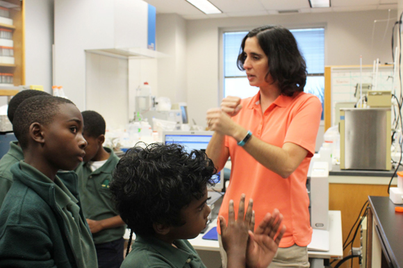 Kelly Quinn explains to Academy Prep students how the water samples they collected will be analyzed in the lab.