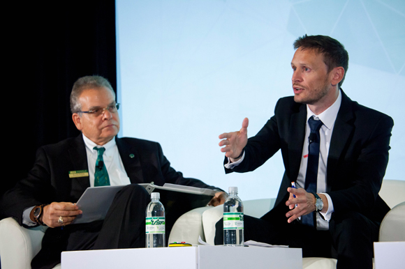Paul Sanberg, left, listens as C�dric Denis-R�mis, vice pres., of development, at PSL University in France gives a talk at the Young Universities Summit.