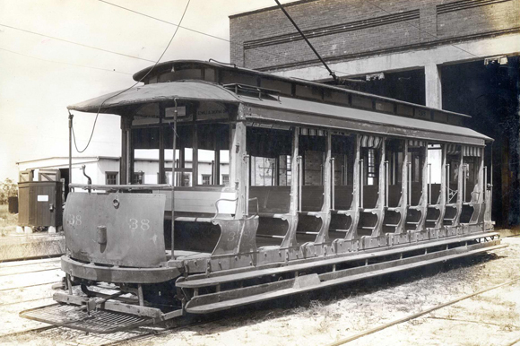 An open-sided streetcar from the early 1900's in front of the streetcar barn, which is now Armature Works.