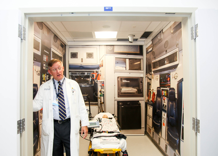 Dr., Paul Danielson, chief, div., of pediatric surgery, stands inside a simulated emergency ambulance for staff, students, and residence.