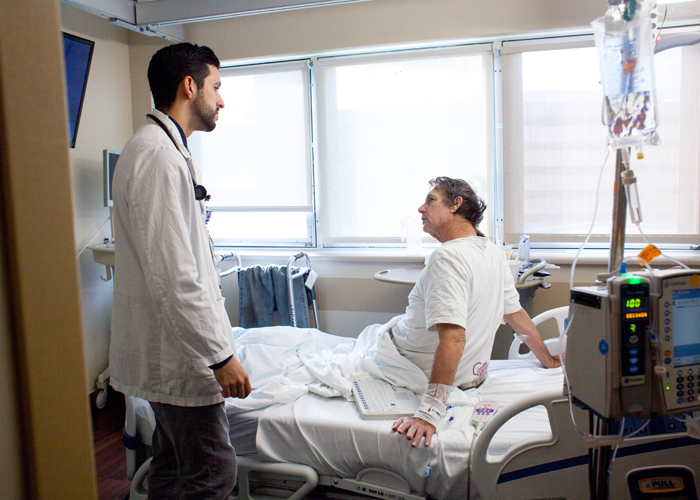 Jesus Diaz Vera, left, informs long-term patient David Pimms that he will be released from the hospital in three days.