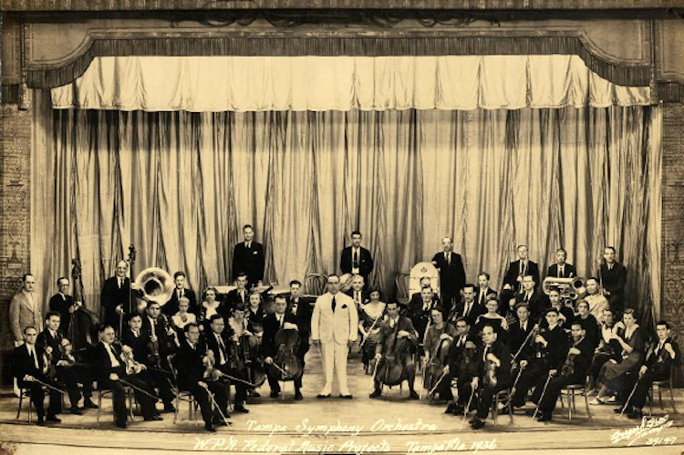Tampa Symphony Orchestra at a building in Ybor with Wilfredo Rodríguez, a violinist in the front row.