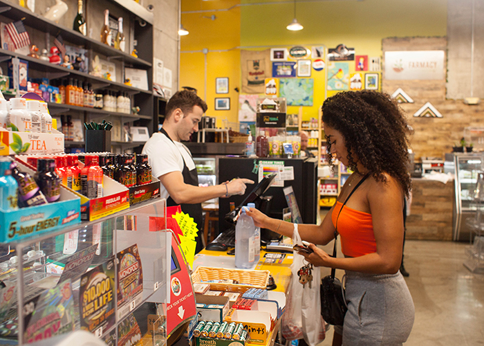 Boris Filui rings up Jasmyne Hill's vegan snack at Duckweed Urban Grocery in downtown Tampa (2018).