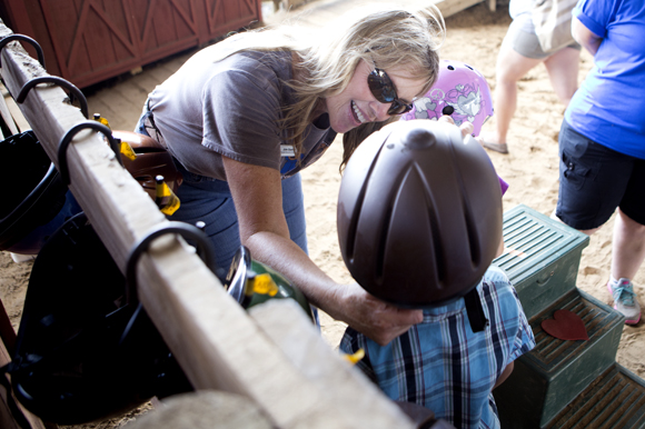 Edie Ebbert Dopking helps Shawn Webber, 7, with his helmet before going for a ride at Quantum Leap Farm.