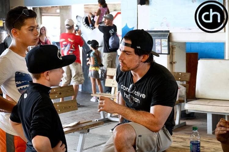 Beau Blouin talks with young participants in a fishing tournament supported by local businesses.