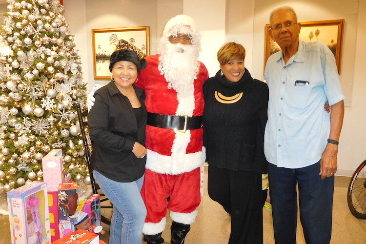 Dana Battle, Woodson Museum board chair, with Santa; Terri Lipsey Scott, executive director; and David McEachern, retired board member of the YMCA.
