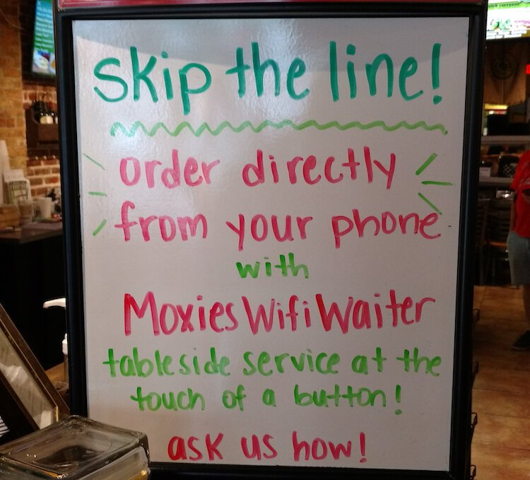 A sign at Moxies Cafe and Caterer introduces visitors to the Wifi Waiter.