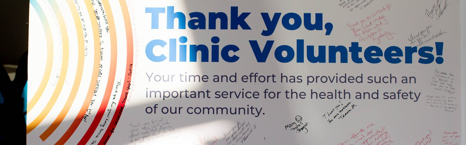 A signed poster thanking volunteers sits at the entry way where patients come in to get vaccines at Metro Inclusive Health Service which serves all people regardless of economic, ethnic, or sexual orientation.