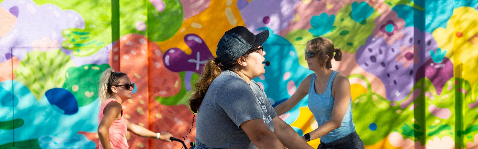 Riki Tarr, left, Monica DeChaine, and Hillary Hepp check out art by Jujmo, a Tampa Bay muralist known for her happy colors and cartoon-like style.