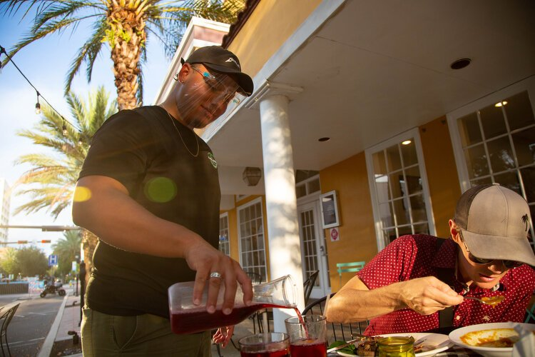 "Matt Lugo pours hibiscus tea for Aaron Clark at Kara Lynn's Kitchen, where organic ""clean food"" is served, made from scratch, and expanded outdoor seating is offered for added safety."