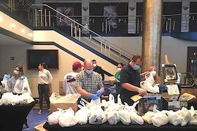 The Mahaffey Theater lobby is serving as a staging area for packing food for hungry kids.
