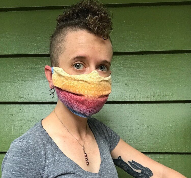 83 Degrees writer Jessi Smith demonstrates the proper nose fit and coverage for a homemade mask, this one designed by Sarasota artist Kari Bunker.