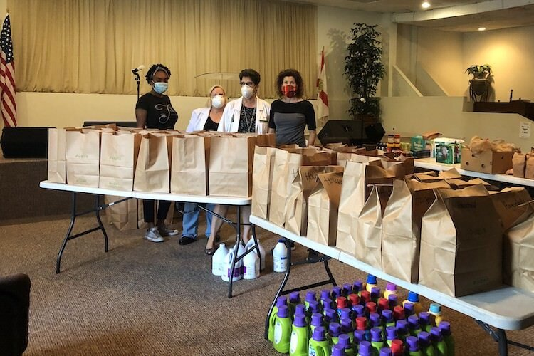 Tramaine Ware, Marcia Johansson, Denise Maguire, and Barbara with the food items and household supplies purchased by USF College of Nursing and the Tampa Police Department to assist Sulphur Springs families during the coronavirus pandemic.