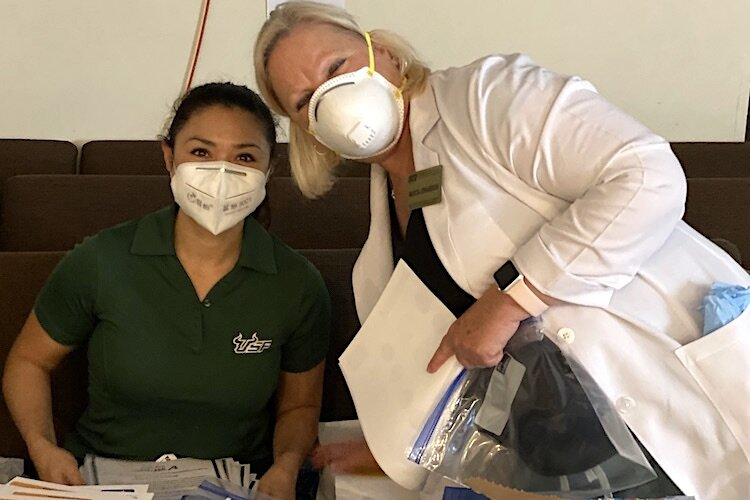 Ann Joyce and Marcia Johansson from the USF College of Nursing behind their COVID-19 PPE at the April 17 event supporting Sulphur Springs families at Abundant Life Church.