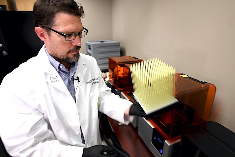 Dr. Jonathan Ford of USF Health examines a batch of newly printed 3D nasal swabs.