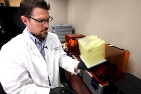 Dr. Jonathan Ford examines a new batch of 3D printed nasal swabs.