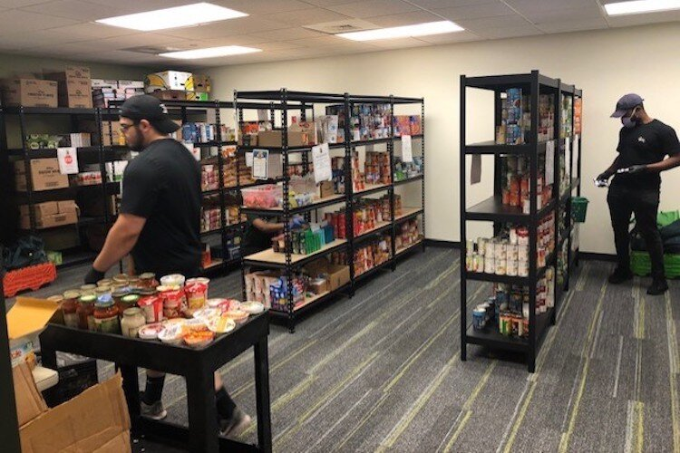 Staff and volunteers restock shelves at USF food pantries with donated food and purchases made using cash donations.