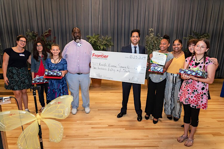 Tony Selvaggio holds the check from Frontier Communications for the Dowdell Middle School student who won the business pitch competition.