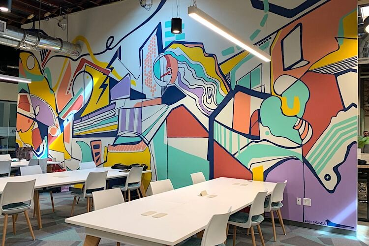 An open collaboration area offers an abstract look at characteristics true to Tampa Bay including lightning bolts, the Riverwalk, and hockey sticks. Mural by Portland-based artist Davey Barnwell.