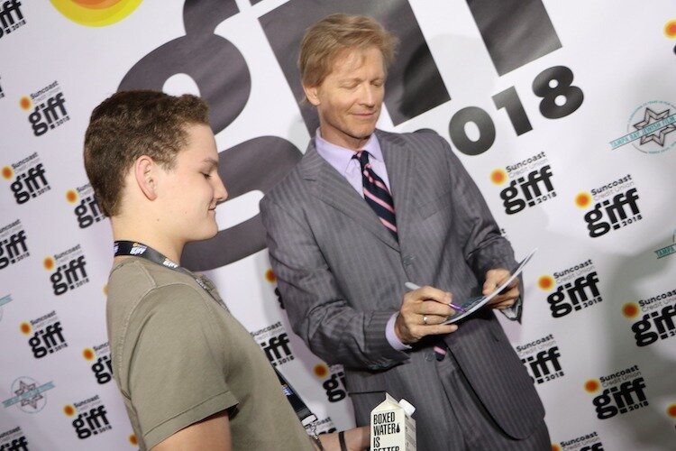 Eric Stoltz autographs memorabilia for a young fan at GIFF 2018.
