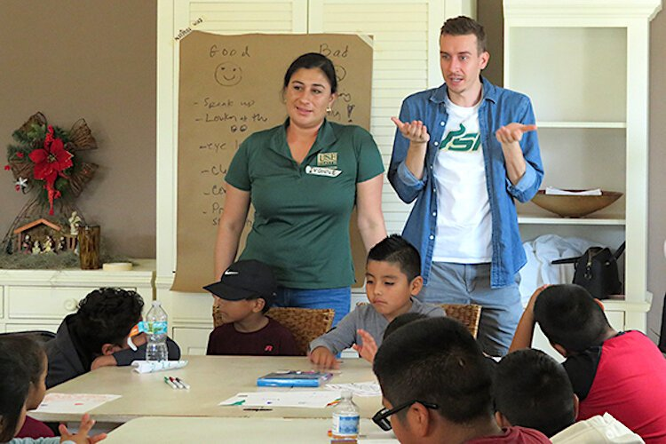 Logan Marx teaches a lesson on good communication skills at the Wholesome Winter Kids Camp alongside USF College of Nursing Assistant Professor Dr. Ivonne Hernandez.