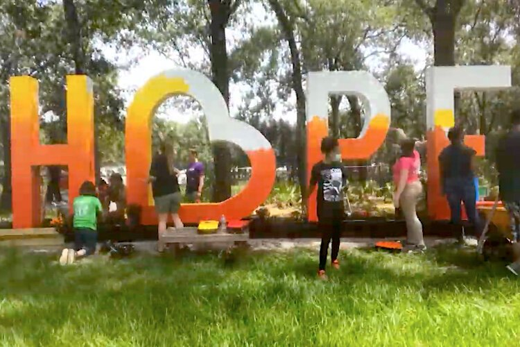 Local students and Uptown Tampa residents team up to paint a Hope sculpture in Harvest Hope Park.