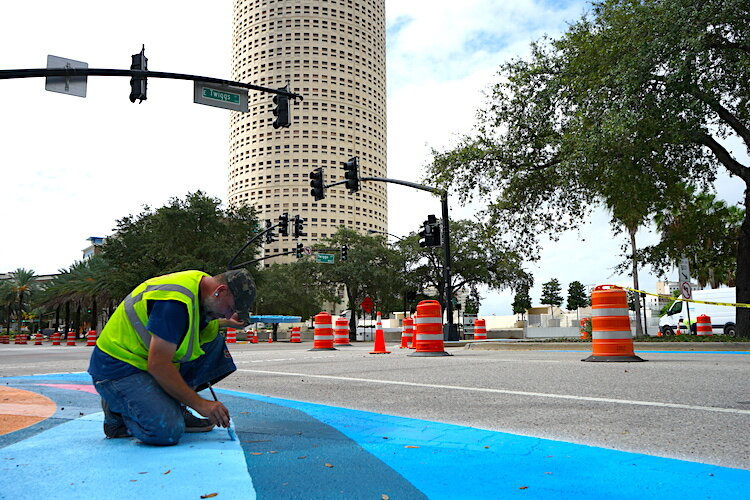 Artists and volunteers help paint portions of Tampa's downtown streets.