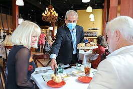 Casa Santo Stefano GM Michael Piazza serves fresh-baked bread to patrons.