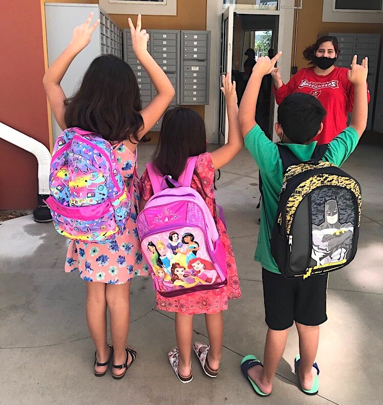 Children living public housing proudly wear new backpacks handed out before school started in September.