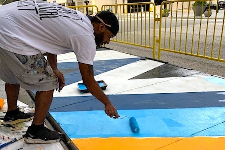 Artist Ron Simmons works his magic to brighten up another parklet.