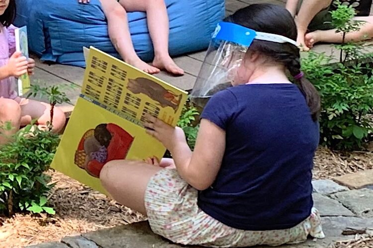 A second-grader reads aloud to preschoolers during summer school.