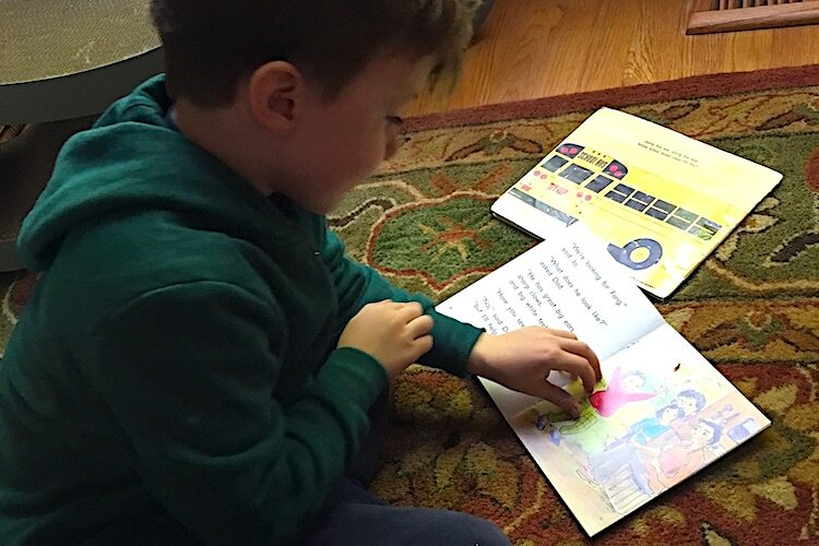 A child practices reading out loud to improve his reading skills.