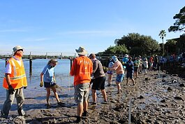 Community members install oyster bags to create a living shoreline in Ozona.