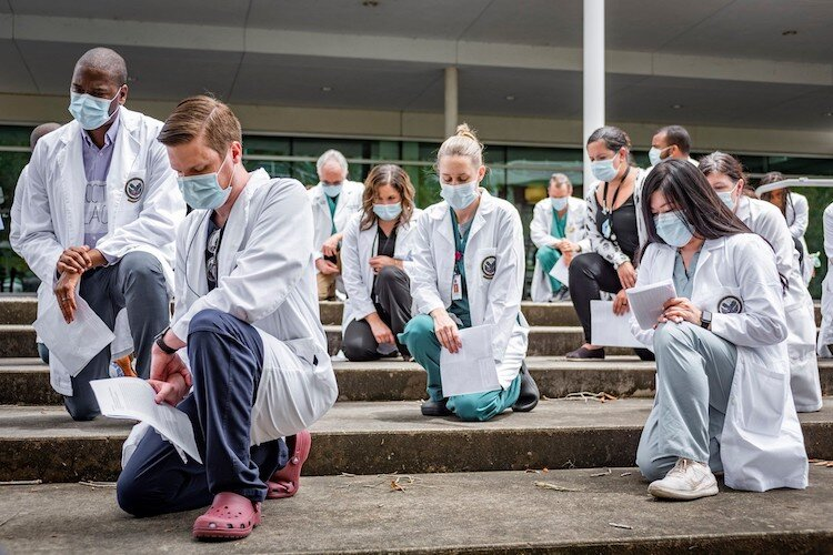 About 150 USF Health staff and faculty participate in #whitecoatsforblacklives protests held across the country.