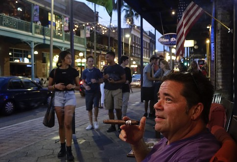 Gary Russo smokes a cigar in front of Taberno Cigars